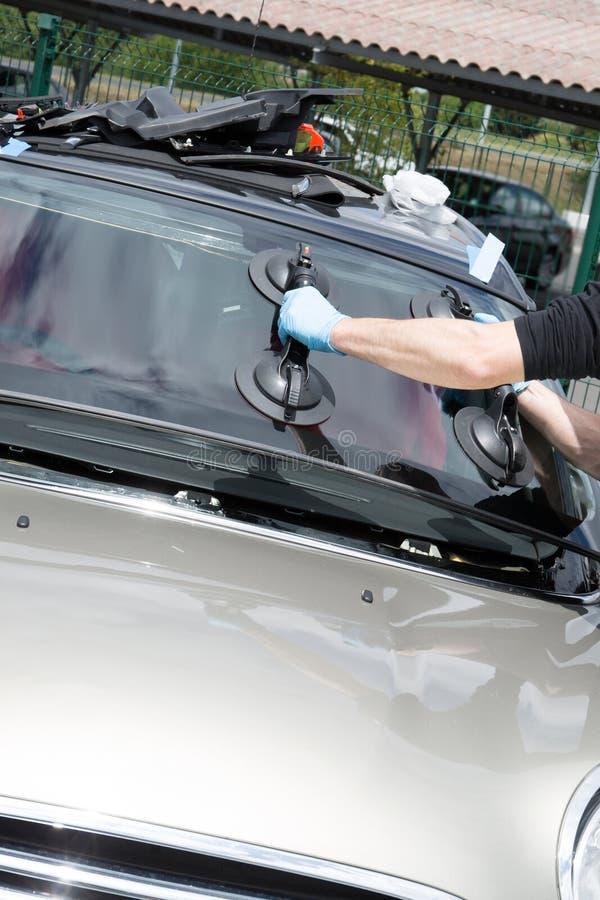 修理和修理打破的挡风玻璃汽车的玻璃剪裁工在顾客街道或工作地点 免版税库存图片