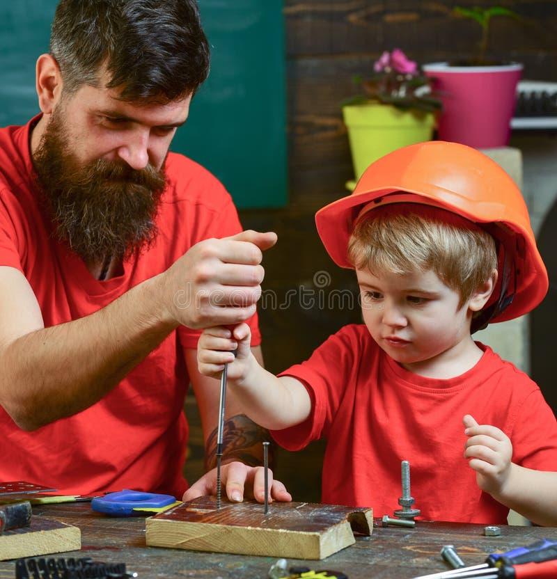 修理和车间概念 生,做父母与教小儿子的胡子使用工具螺丝刀 男孩,繁忙的孩子  免版税库存照片