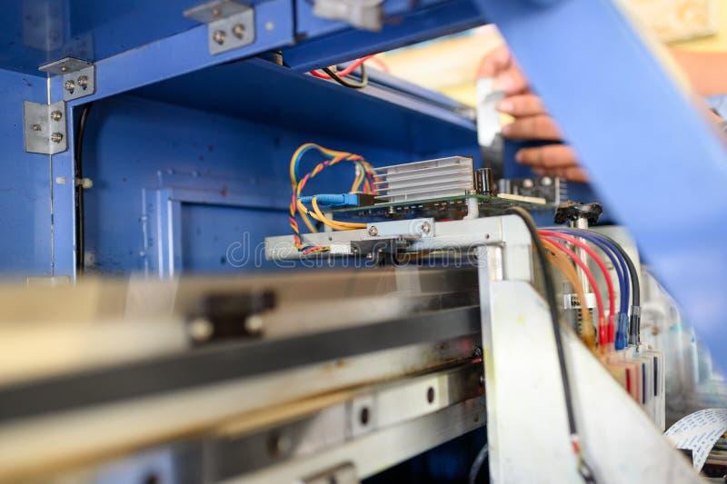 修理喷墨打印机颜色分配器的mainboard技术员  免版税库存照片