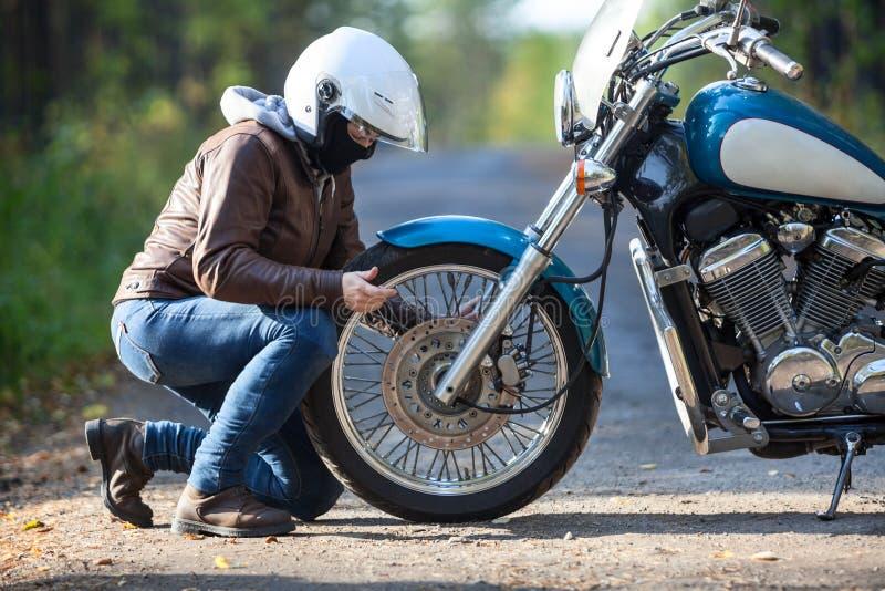 修理在一辆摩托车的妇女一个spoked轮子在土乡下路 免版税库存照片