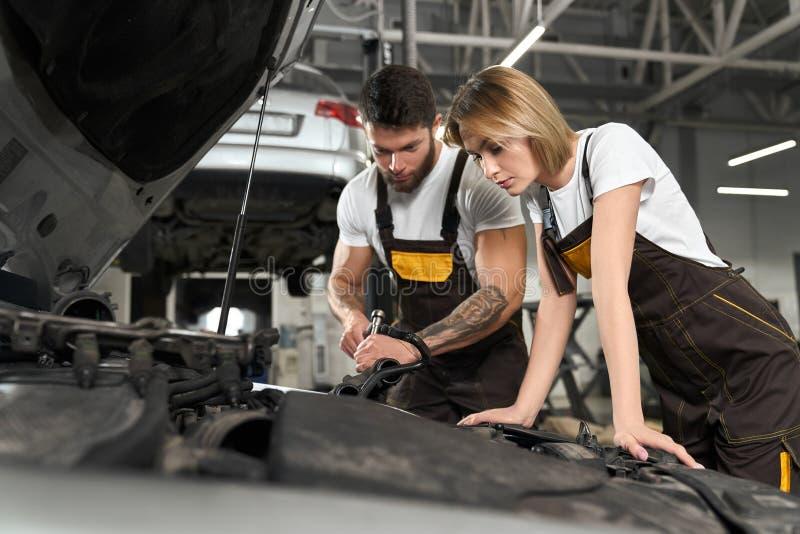 修理在专业autoservice的两位技工汽车 库存图片
