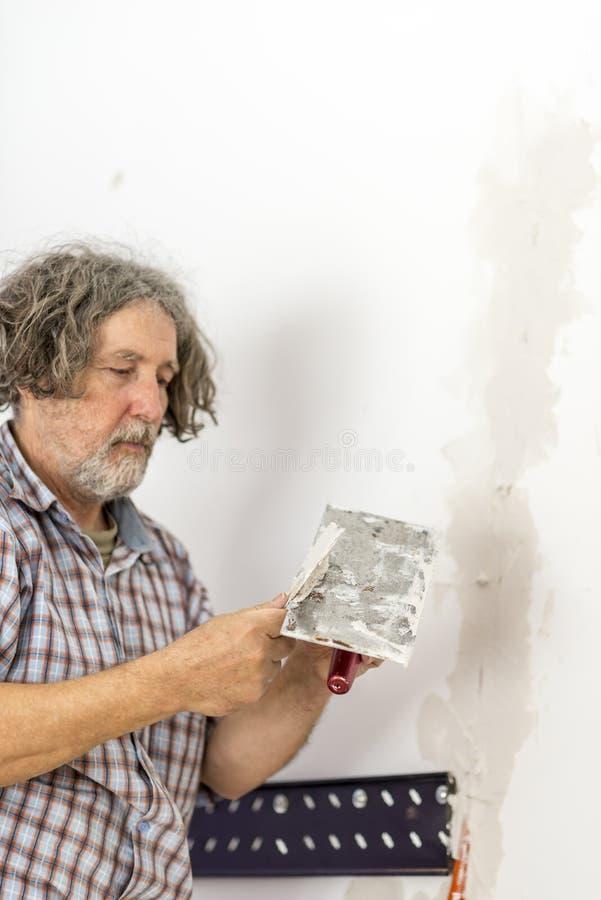 修理在墙壁的建造者一个裂缝 免版税图库摄影