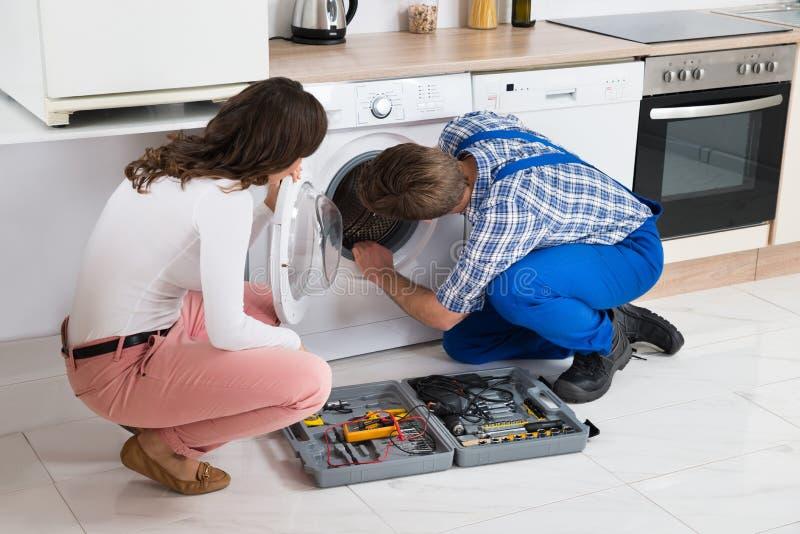 修理在妇女前面的安装工洗衣机 免版税图库摄影