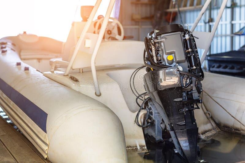 修理在小船车库的可膨胀的汽艇引擎 船引擎季节性服务和维护 有开放盖子的船马达 库存图片