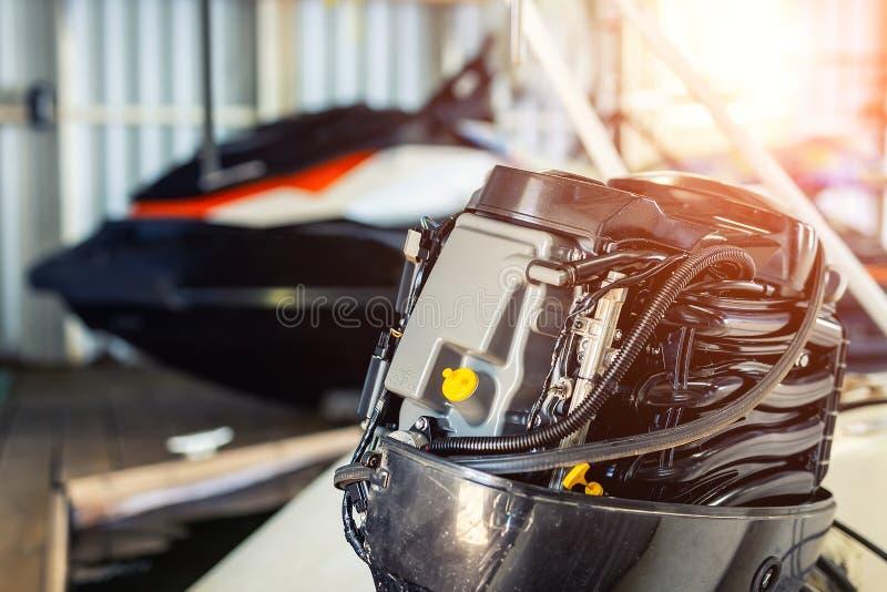 修理在小船车库的可膨胀的汽艇引擎 船引擎季节性服务和维护 有开放盖子的船马达 免版税库存图片