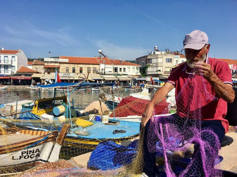 修理在港口和小船口岸观点的渔夫渔网的老Foca,伊兹密尔 由于漂浮在镇的海的封印, 库存图片