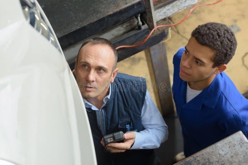 修理在车库的两位技工汽车在汽车下 库存图片