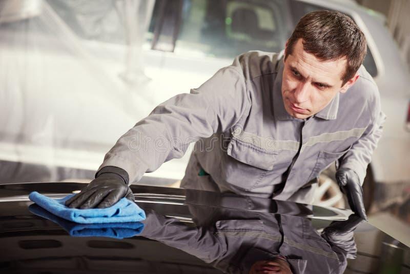 修理在车库的人工作者擦亮的汽车车身 库存图片