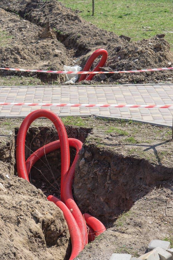 修理地下通信管子在公园 图库摄影