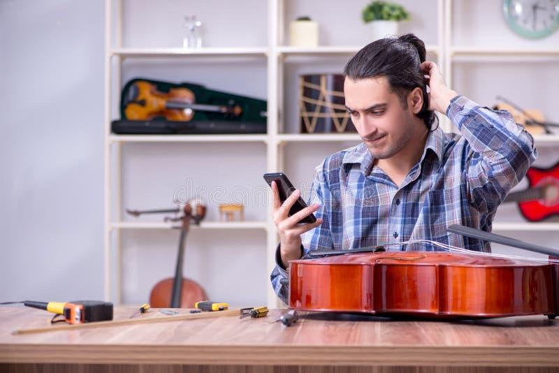 修理大提琴的年轻英俊的安装工 免版税库存照片