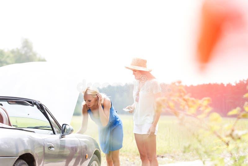 修理失败的汽车的朋友在晴天 免版税库存图片