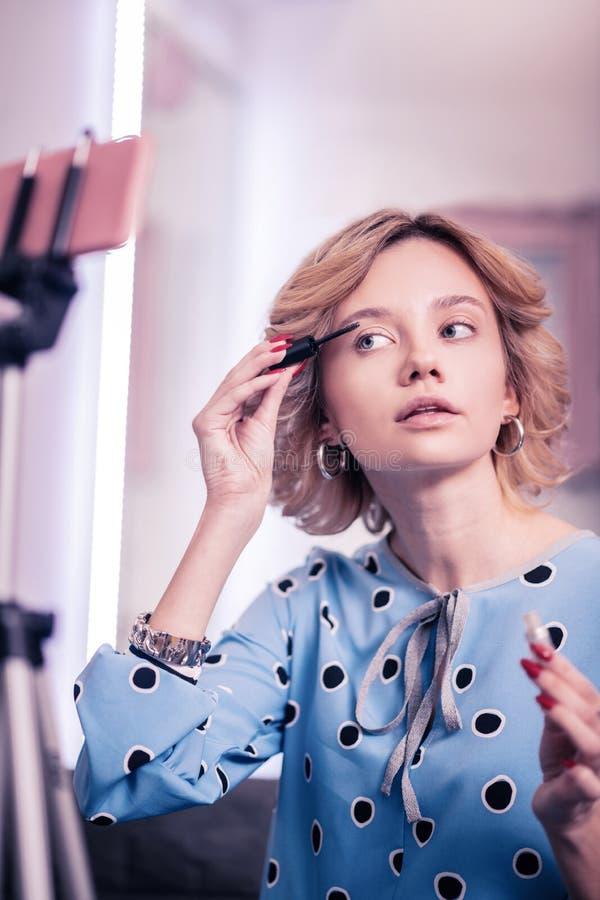修理她的有胶凝体的白肤金发的博客作者眼眉,当摄制录影时 免版税库存图片