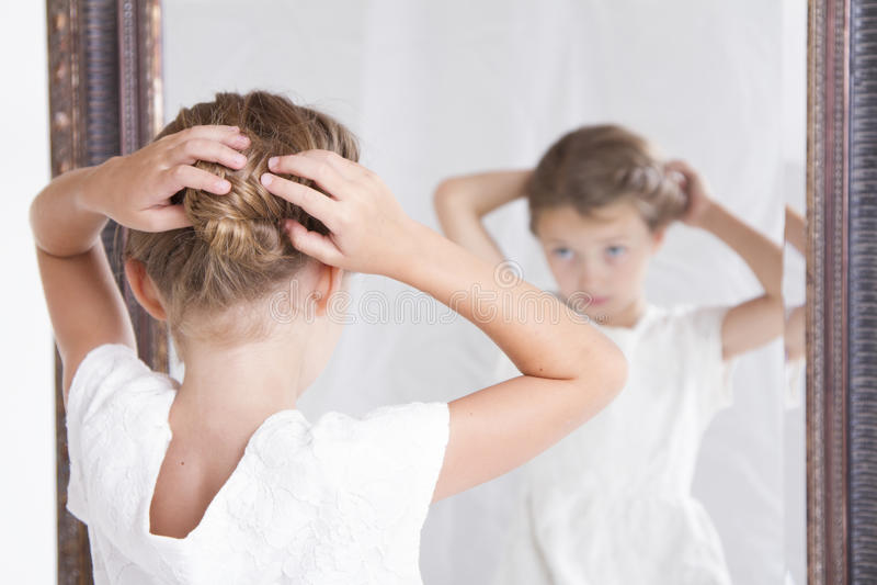 修理她的头发的孩子,当看在镜子时 免版税库存照片