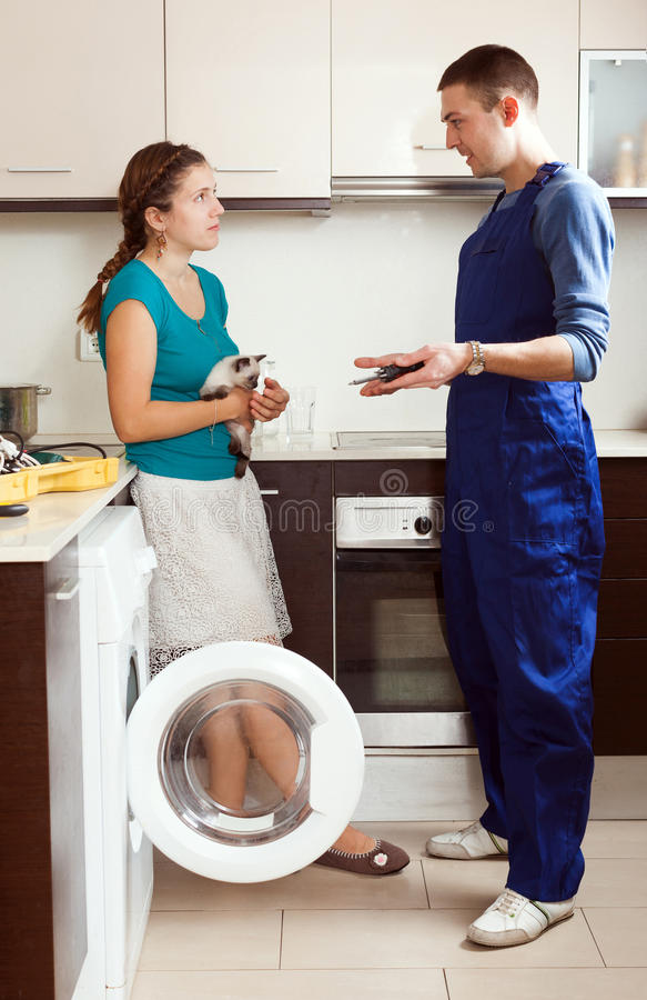 修理妇女的工作者一台洗衣机 免版税库存图片