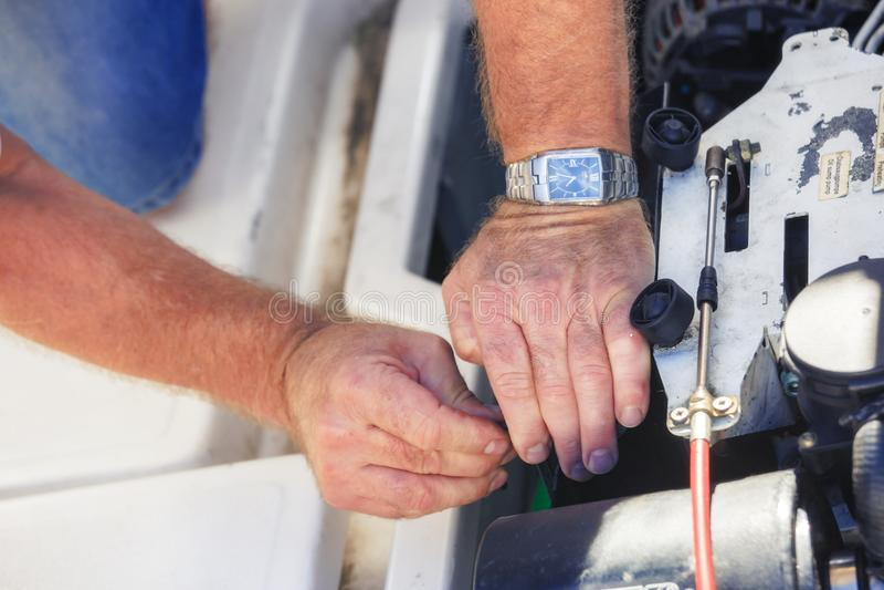 修理小船引擎的技工手 免版税库存照片