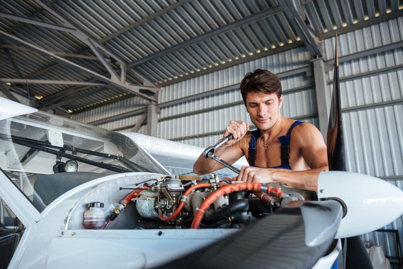 修理小飞机的严肃的年轻飞机机械员 库存图片