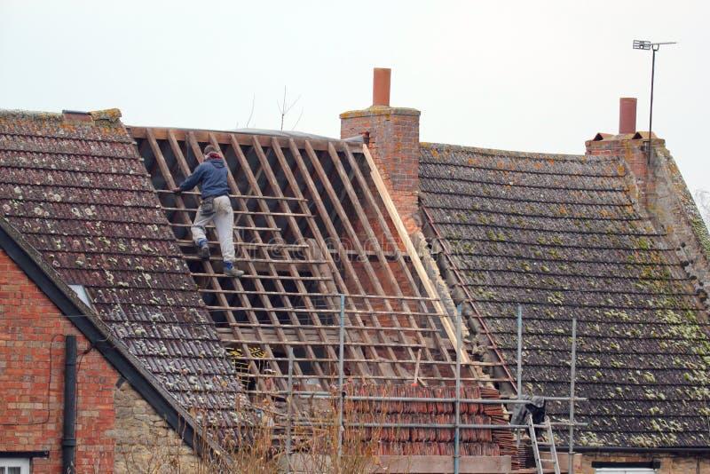 修理屋顶的屋面防水工。 库存图片