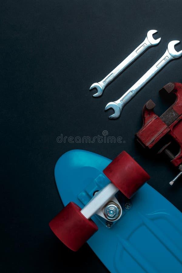 修理工具和蓝色滑板,在灰色背景上,上面有红色轮子 免版税图库摄影