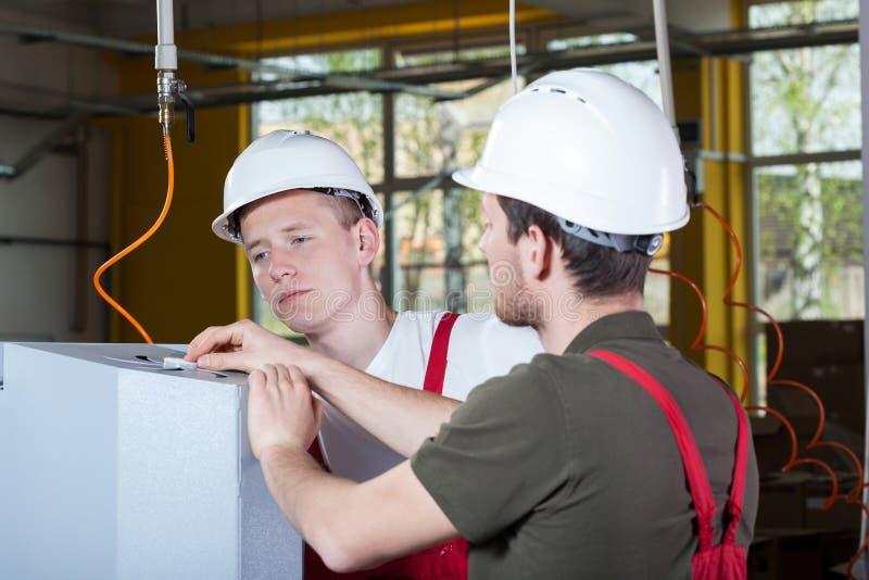 修理工厂机器的两位专家 库存图片