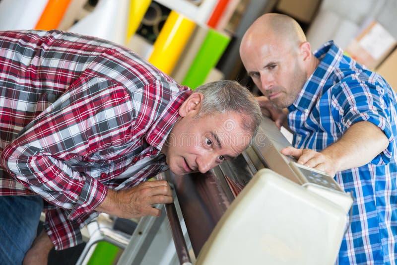修理影印机失败的公司的技术员 免版税库存照片