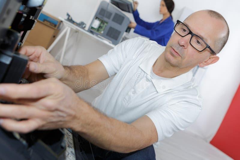修理打印机的男性高级技术员在办公室 免版税库存图片