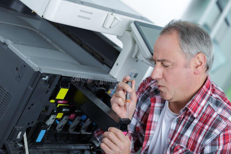 修理打印机的男性高级技术员在办公室 图库摄影