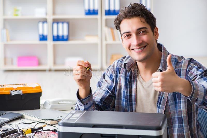 修理打破的打印机传真机的硬件安装工 免版税库存图片