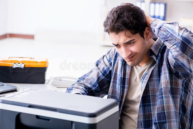 修理打破的打印机传真机的硬件安装工 库存照片
