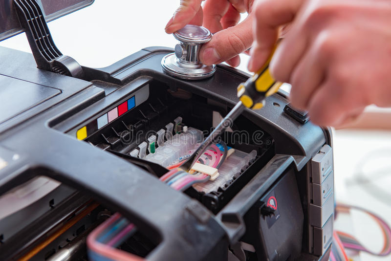 修理打破的彩色打印机的安装工 库存照片