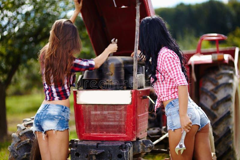 修理拖拉机的性感的女性农夫 图库摄影