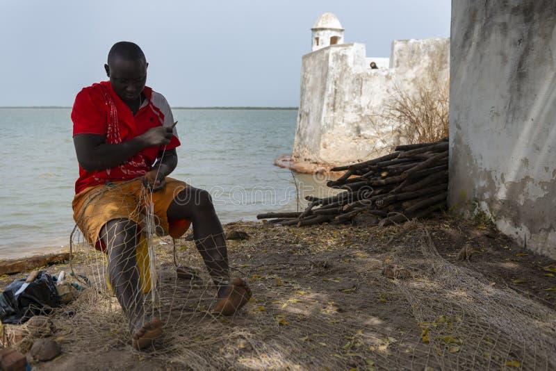 修理捕鱼网的渔夫在卡谢乌堡垒旁边在市卡谢乌,在几内亚比绍 免版税库存图片