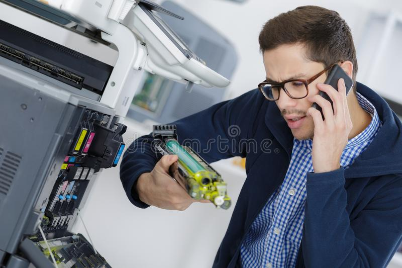 修理数字复印机机器的年轻男性技术员 免版税库存照片