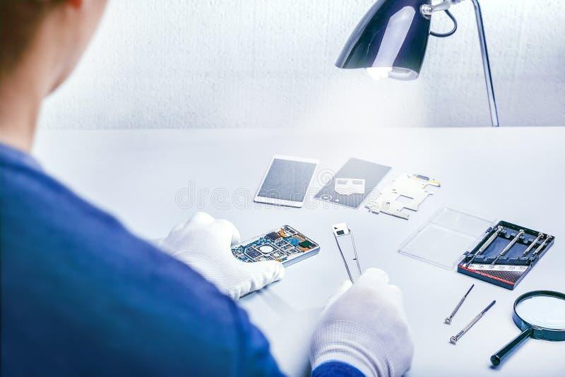 有镊子的安装工拆卸的智能手机 修理智能手机,服务中心,技术员,手机,装置,电镀物品 免版税库存照片