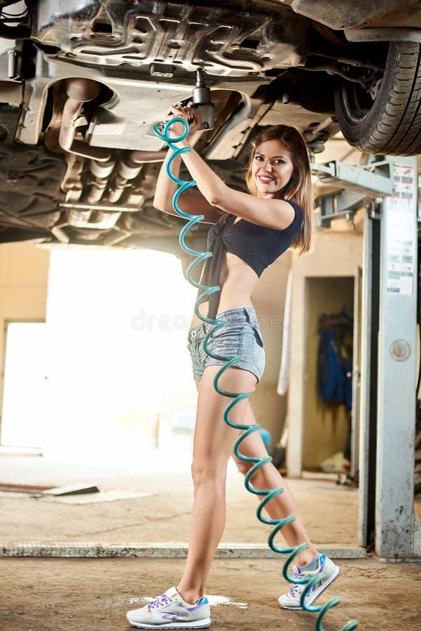 修理有气动力学的钥匙的式样女孩汽车在液压悬挂 免版税库存图片