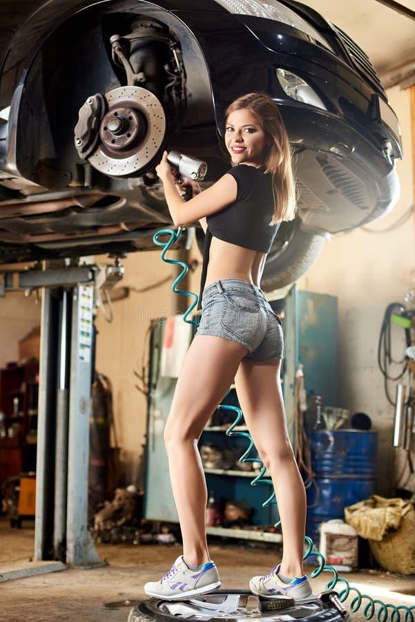 修理有气动力学的钥匙的运动女孩汽车在液压悬挂 图库摄影
