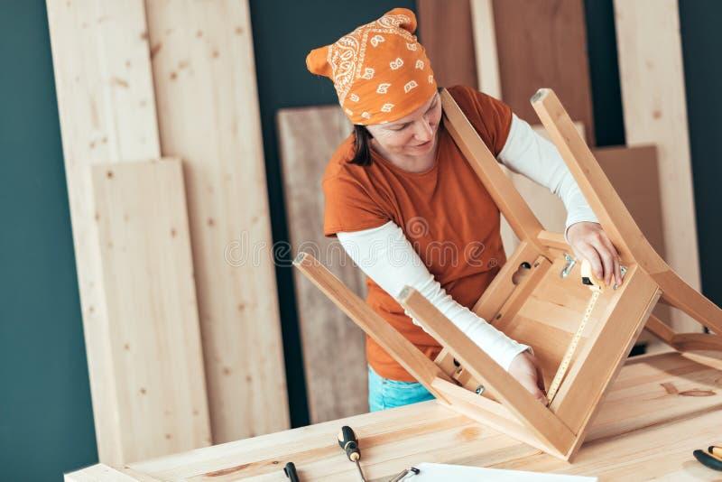 修理木椅子位子的女性木匠在车间 图库摄影
