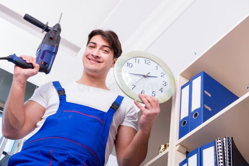 修理架子的年轻工人在办公室 免版税库存图片