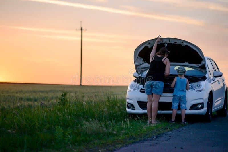 修理某事在他们的汽车的母亲和儿子 免版税库存图片