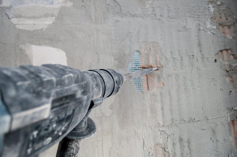 修理概念,修理工具,有做在墙壁的电锤钻子的建造者工作者孔在公寓 电钻 perforat 图库摄影