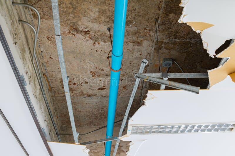 修理泄漏在下面石膏天花板内部办公楼的水管 库存照片