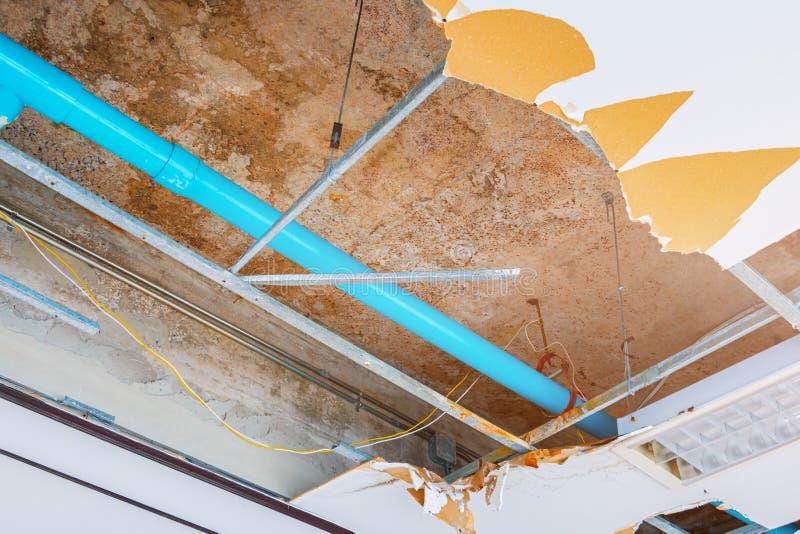 修理泄漏在下面石膏天花板内部办公楼的水管 免版税库存图片