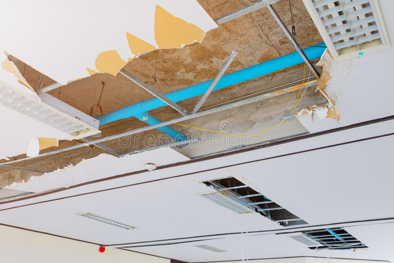 修理泄漏在下面石膏天花板内部办公楼的水管 库存图片