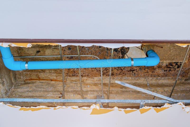修理泄漏在下面石膏天花板内部办公楼的水管 免版税库存照片