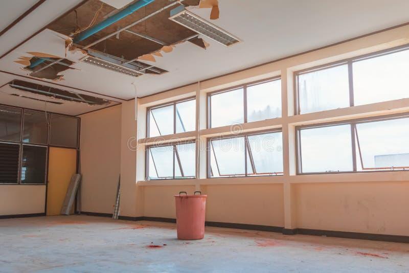 修理泄漏水管在下面石膏天花板内部办公楼和桶水中 免版税库存图片