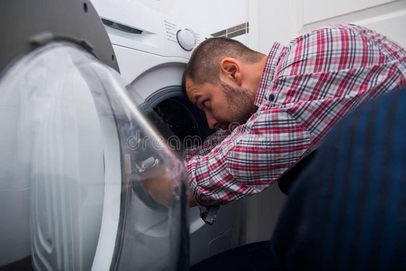 修理洗衣机的帅哥在卫生间里 免版税库存照片