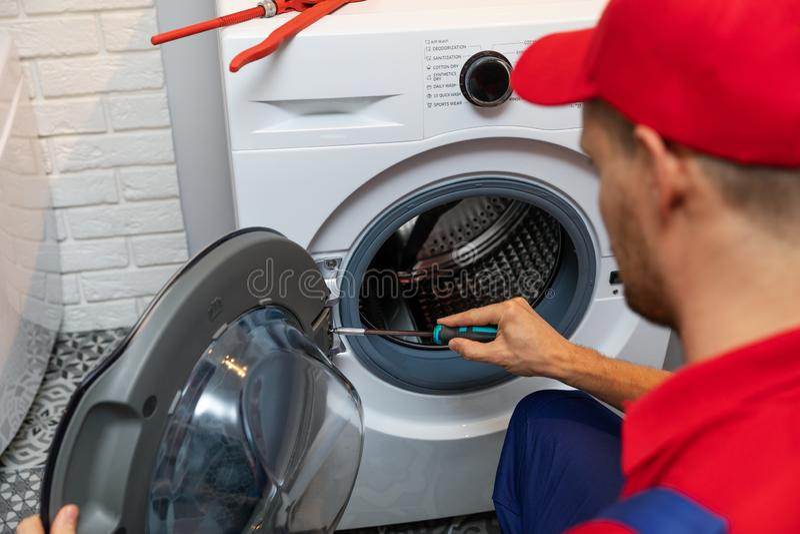 修理洗衣机门的安装工 免版税库存照片