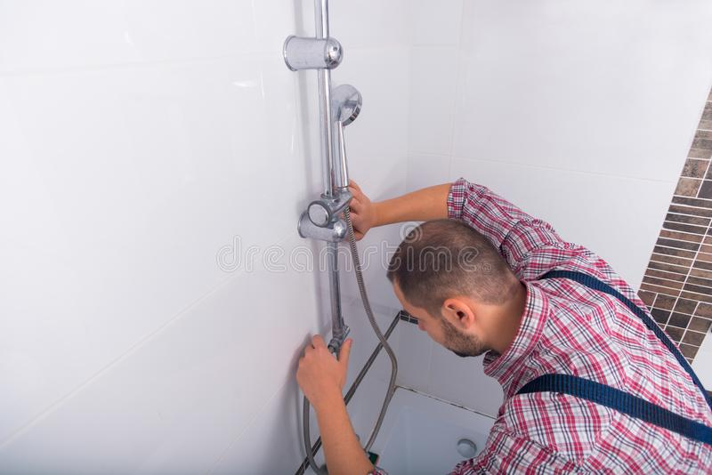 修理淋浴喷头的杂物工在卫生间里 免版税库存图片