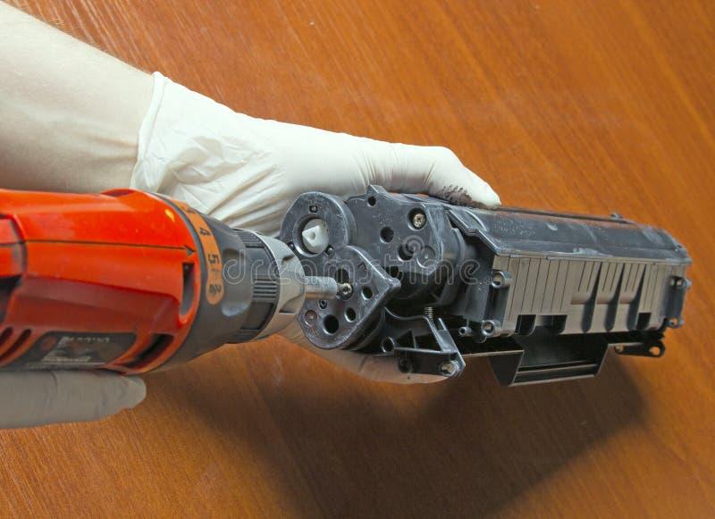 修理激光墨粉盒的手 免版税库存照片