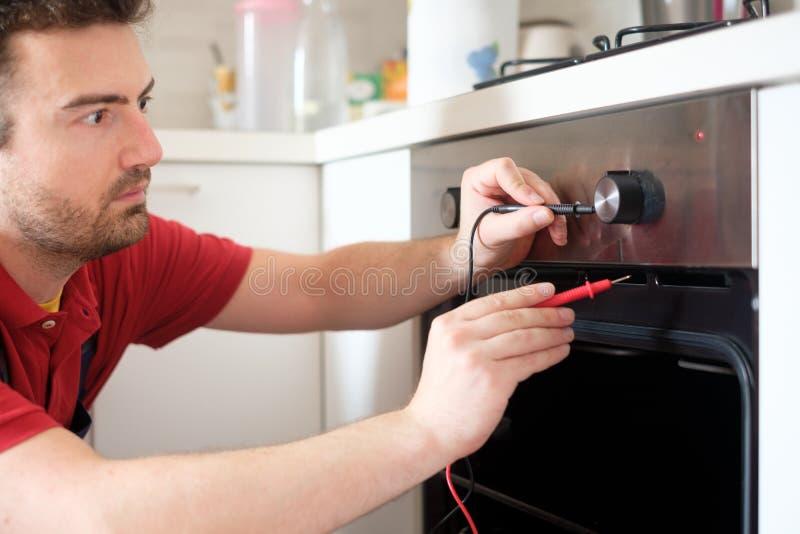 修理烤箱的工作者在厨房里 免版税库存照片