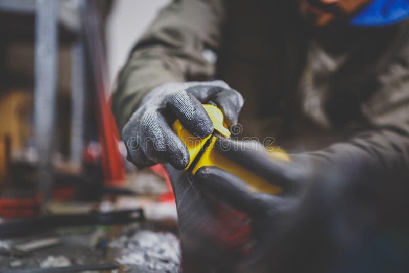 修理石头,边缘的男性工作者削尖在滑雪服务车间,滑雪的滑动面 削尖一mo的边缘 免版税库存照片